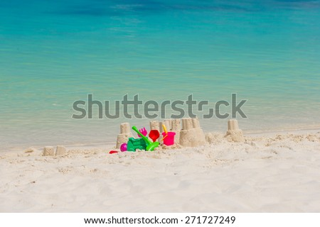 Sandcastle at white beach with plastic kids toys background the sea - stock photo