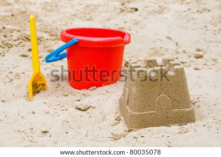 Sandcastle with bucket and shovel - stock photo