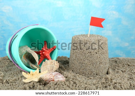 Sandcastle with flag and plastic bucket on sandy beach on sea background - stock photo