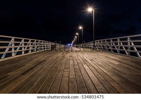 Sandgate pier with a dark night sky, Brisbane. Perspective to the hut structure with leading lines from the textured wooden flooring.