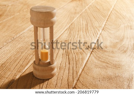 Sandglass on the wooden table - stock photo