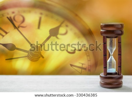 Sandglass on the wooden table - stock photo