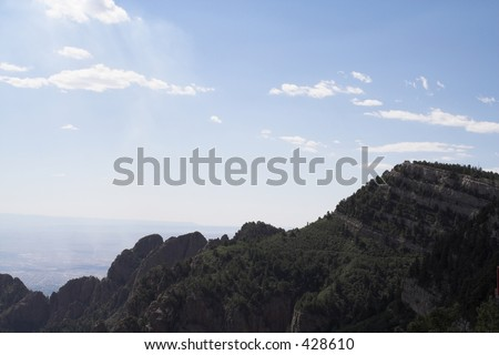 Sandia peak against blue sky and white clouds - stock photo
