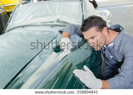 Sanding down a car - stock photo