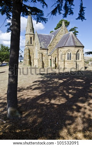 Sandstone church framed by tree.  Wesley Church, (now the Uniting Church) Ross, Tasmania, Australia. The church was built in 1885. - stock photo