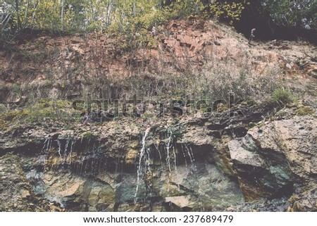 sandstone cliffs with water source. latvia. - retro, vintage style look - stock photo