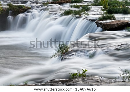 Sandstone Falls, a waterfall on West Virginia's New River, cascades over boulders and rock ledges in evening light. - stock photo