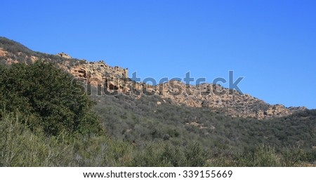 Sandstone geology towering above chaparral, Thousand Oaks, CA - stock photo