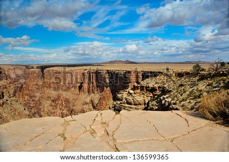 Sandstone rocky ledge and a 1000 foot drop off in the northern arizona desert on a beautiful fall day - stock photo