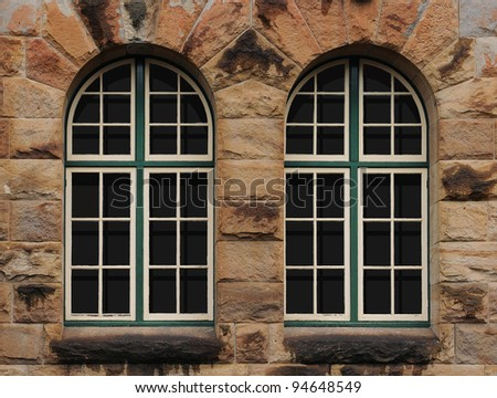 Sandstone Texture wall with old windows - stock photo