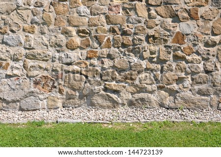 Sandstone wall and green grass - stock photo