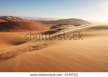 Sandstorm in Erg Chebbi sand dunes at sunrise in the Sahara Desert (Hassi Labiad and Merzouga, Morocco). Algeria is located 20 km from here. - stock photo