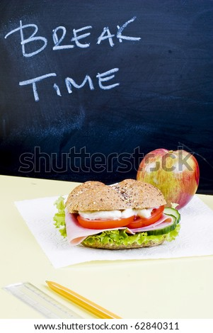 Sandwich and apple on classroom table - breakfast - stock photo