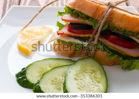 sandwich cucumber and lemon on a white plate