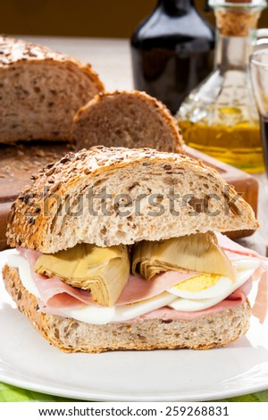 sandwich filled with ham, eggs and artichokes in oil - stock photo