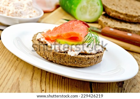 Sandwich from rye bread with cream, cucumber, dill and salmon on an oval plate on a wooden boards background - stock photo