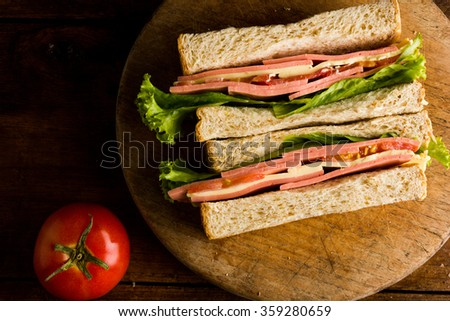 Sandwich ham cheese, whole grain bread, organic salad, cheese, fresh tomato and ham - stock photo