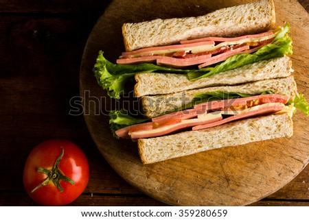 Sandwich ham cheese, whole grain bread, organic salad, cheese, fresh tomato and ham - stock photo