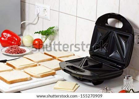 Sandwich maker, toasts and vegetables on the table. - stock photo
