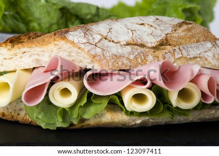 Sandwich of cold cuts, cheese and lettuce - stock photo