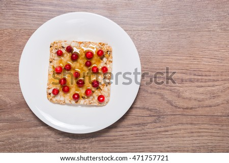 Sandwich of crispy bread, honey and cranberries on the saucer