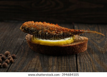 sandwich of rye bread with fried fish and lemon on a wooden background