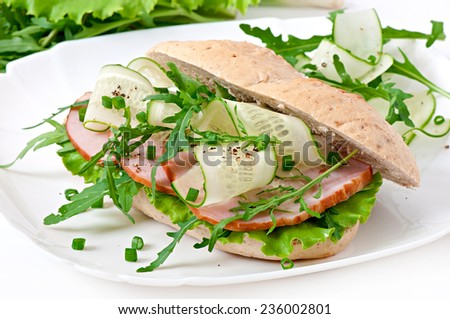 Sandwich of wholemeal bread, ham, cucumber and arugula