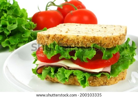 Sandwich on a white plate with ham, tomato, lettuce and cheese - stock photo