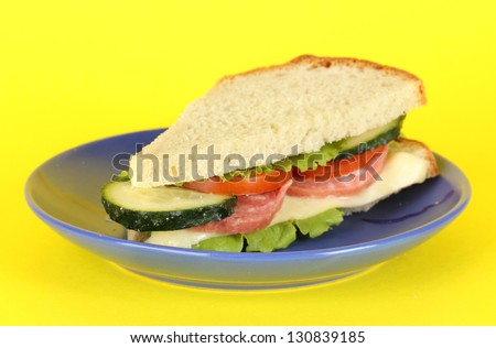 Sandwich on plate on yellow background