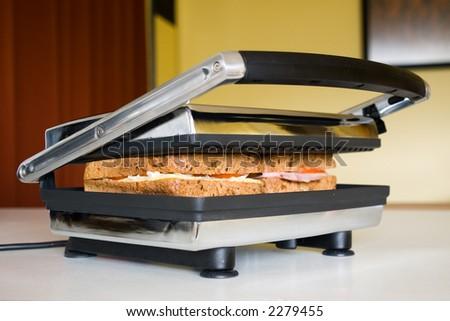 Sandwich press in use in modern kitchen - stock photo