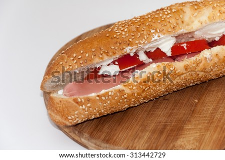 Sandwich roll with hot dog tomato cow cheese.