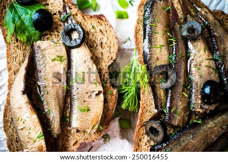 Sandwich, tapas with sardines, sprats with olives and herbs - stock photo