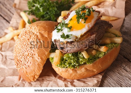 Sandwich with beefsteak, fried egg and French fries close-up. Horizontal