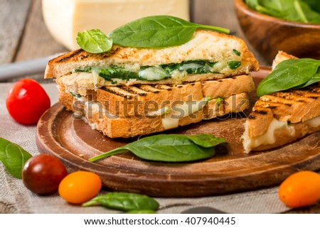 sandwich with cheese and spinach on wooden background, close up - stock photo