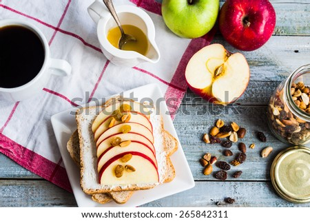 sandwich with cheese, apple and dried fruit, a cup of coffee, a healthy breakfast, top view - stock photo