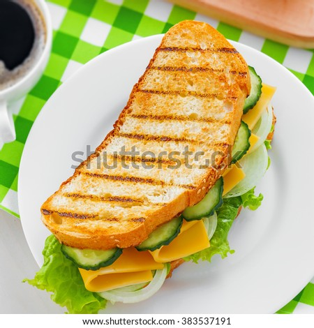 Sandwich with cheese, lettuce and vegetables for breakfast with coffee, top view