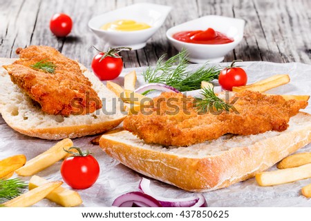 sandwich with ciabatta and bread crumb coated fried pork chop with french fries, red onion, cherry tomatoes and dill on a parchment paper, view from above, close-up  - stock photo