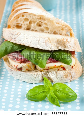 Sandwich with Deli Meat and Cheese and Fresh Basil - stock photo