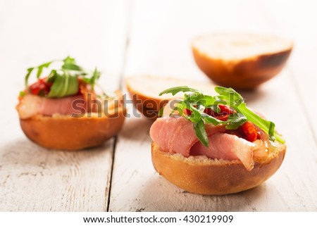 Sandwich with duck breast and arugula on a white wooden table