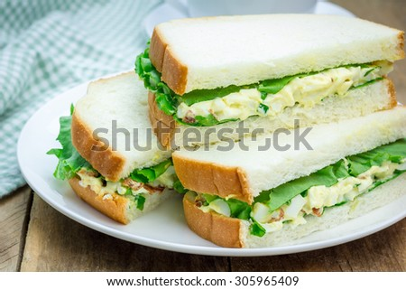 Sandwich with egg salad, bacon, green onion and lettuce - stock photo