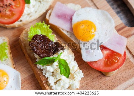 Sandwich with egg, tomato, greens, homemade cheese and ham on wooden background