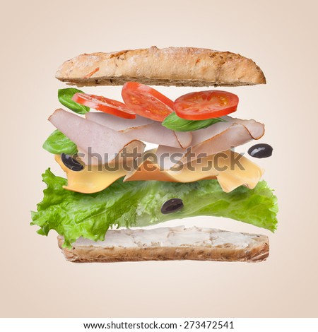 Sandwich with falling ingredients in the air - slices of fresh tomatoes, ham, cheese and lettuce - stock photo