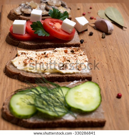 Sandwich with feta cheese, tomatoes, black olives, mushrooms, cucumber and fresh herbs. Appetizers with different fillings selective focus. - stock photo