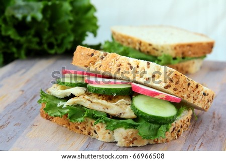 Sandwich with fresh vegetables and chicken on a wooden board - stock photo