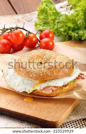 Sandwich with fried bacon and egg on a chopping board - stock photo