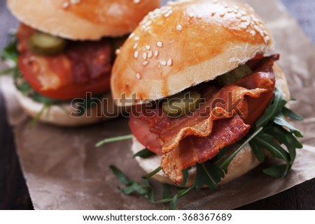 Sandwich with fried bacon, tomato and rocket salad - stock photo