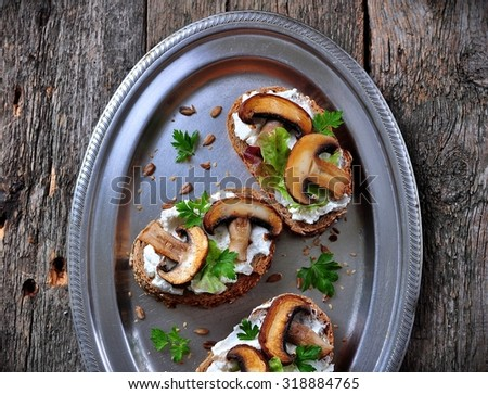 sandwich with goat cheese, roasted mushrooms and lettuce on an iron tray. rustic style - stock photo