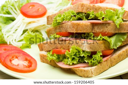 sandwich with ham and tomato on plate - stock photo