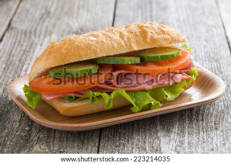 sandwich with ham and vegetables on wooden table, close-up, horizontal - stock photo