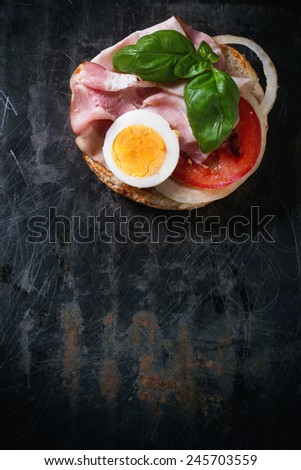 Sandwich with ham, eggs, vegetables and ketchup over black metal background. Top view - stock photo